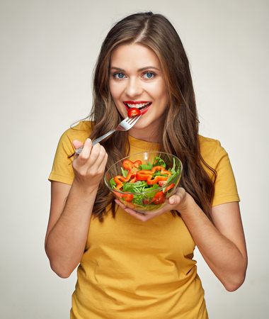 smiling woman eatin vegatable salad with fork. isolated portrait girl with healthy teeth.