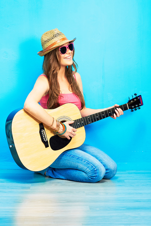 Music woman portrait with guitar. Blue background.