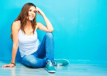 jonge lachende vrouw zittend op de vloer tegen de blauwe muur. hipster stijl. Stockfoto