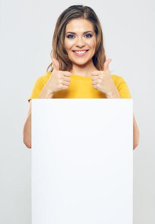 portret van lachende vrouw met witte leeg bord bord. vrouwelijk model toothy lachend. duim omhoog toon jonge vrouw.