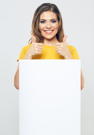 portrait of smiling woman holding white blank sign board. female model toothy smiling. thumb up show young woman. Foto de archivo