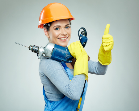 Woman builder with drill tool shows thumb up. Isolated portrait on gray back.