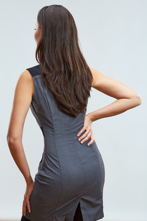 back ache: Concept of occupational diseases office worker. Woman touching back spin with pain. Studio isolated. Stock Photo