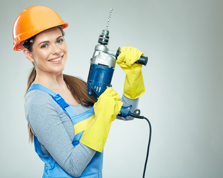 Woman builder portrait with drill tool. Smiling girl hard work concept portrait. Stock Photo