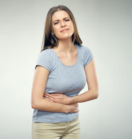 Vrouw met maagpijn wat betreft buik. Geïsoleerde portret. Stockfoto