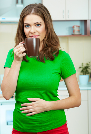 tea hot drink: Portrait of young woman holds a cup with coffee or tea against kitchen background.