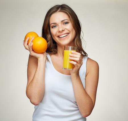 gezond levensstijlportret van het glimlachen van de sportieve die vitamine van de vrouwenholding met jus d'orange en fruit wordt geplaatst. studio geïsoleerd. Stockfoto