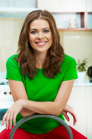 modern living room: Portrait of smiling woman sitting in kitchen on a chair. Clothes of green color. Stock Photo