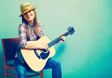 Singing young model play acoustic guitar. Fashion country style. Stock Photo
