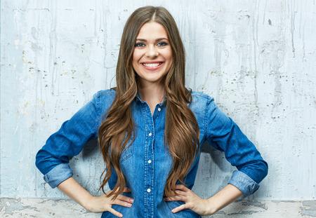 Glimlachend jong vrouwenportret tegen grijze muur. Lang haar.