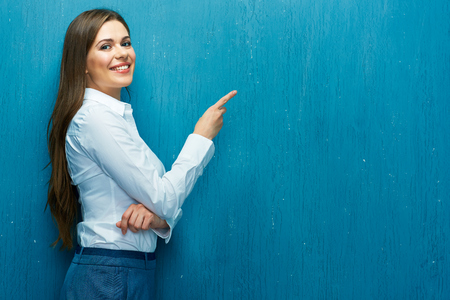 Smiling business woman pointing finger at copy space. White shirt. Long hair. Blue wall.