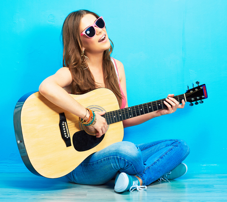 girl sings and playing guitar . musician with acoustic guitar