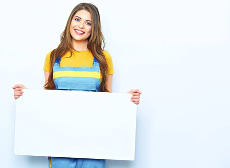 Smiling woman hold sign board. Portrait of smiling builder woman dressed on blue coverall on white background.