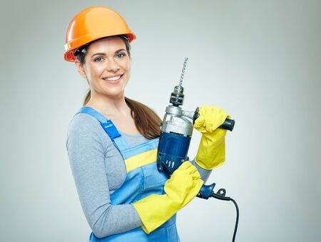Smiling woman wearing helmet holding drill tool. Isolated portrait.