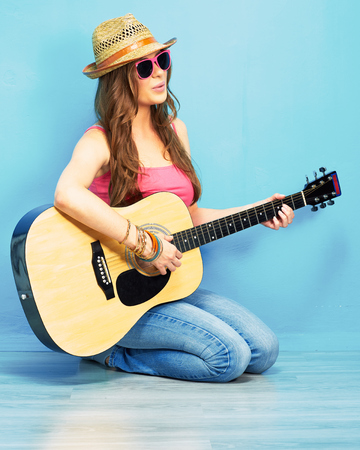 girl play music on acoustic guitar . hipster style portrait of young woman .