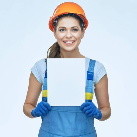Builder holding white banner with copy space. Smiling woman coverall wearing isolated portrait.