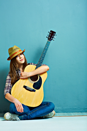 Teenager girl seating on a floor with acoustic guitar.