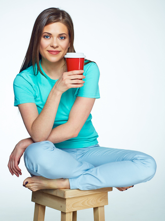sitt: Beautiful girl with long hair sitting on chair with coffee cup. Isolated background. Stock Photo