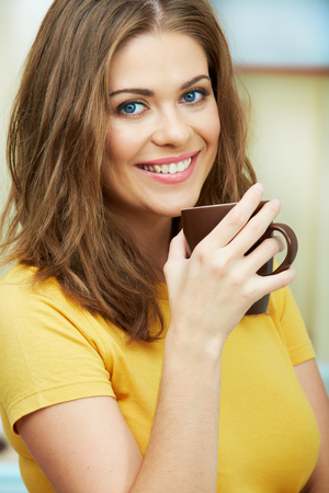 tea hot drink: Portrait of young woman holds a cup with coffee or tea against kitchen background. Close up female face.