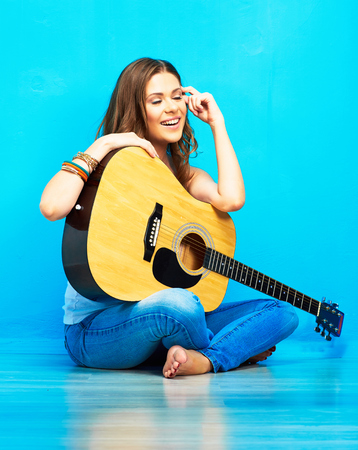 young model girl with acoustic guitar against blue wall background