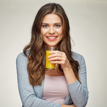 beautiful woman holding orange juice glass. smiling girl isolated portrait. casual clothes. Stok Fotoğraf