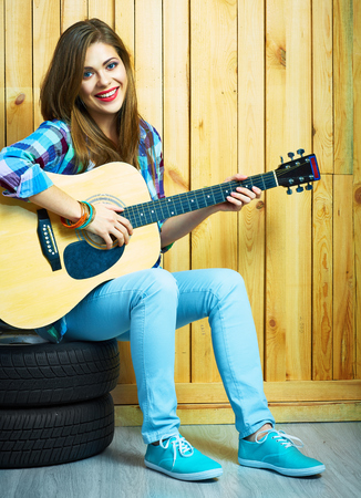 white wood floor: Girl musician play on acoustic guitar. Portrait of young model in hippie style.