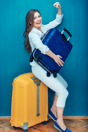 Smiling woman traveler sitting on yellow suitcase and holding blue bag. When a woman wants to take a vacation only the most necessary.
