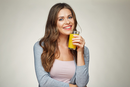 hapyy woman drink orange juice. girl with long hair isolated portrait.