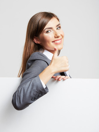 Smiling business  woman leaning on big blank board . Close up female face portrait with arms on blank card. Thumb up. Stock Photo