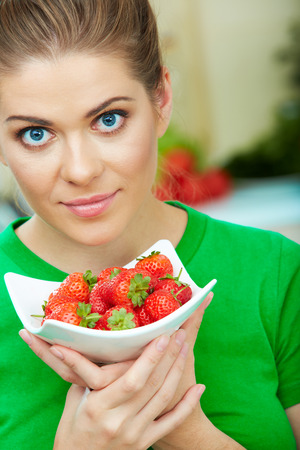 Young woman with red strawberry. Close up female face  portrait. Healthy mel on a plate.