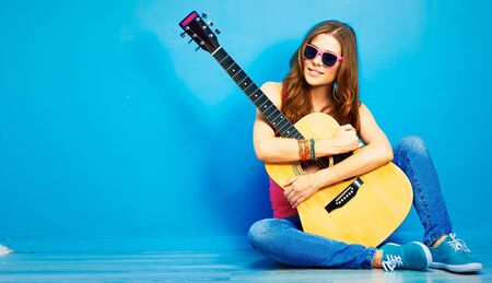 girl with guitar against blue . hipster style portrait of young woman .