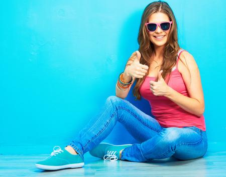 vrouw in jeugdstijl zittend op een vloer toon duim omhoog. Stockfoto
