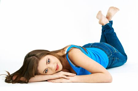 Full body woman portrait. Model with long hair lying on a white floor. Stock Photo