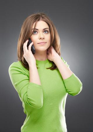 Het portret van telefoon sprekende vrouw kleedde zich in een groene die blouse, op grijze achtergrond wordt geïsoleerd