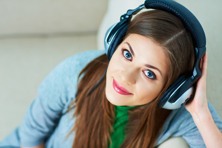mp3 player: Woman listening music with headphones at home. Happy girl.