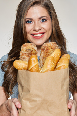 Close up face portrait of smiling woman holding paper bag with baking. Isolated female portrait. Italian bread.