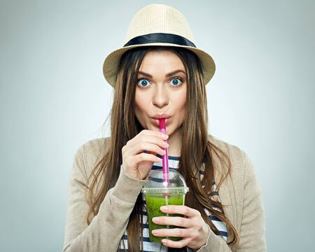 Funny girl drinking green smoothie. Isolated studio portrait.