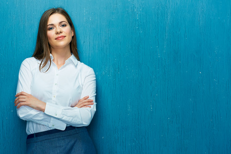 Smiling business woman with crossed arms portrait on blue wall. White shirt.