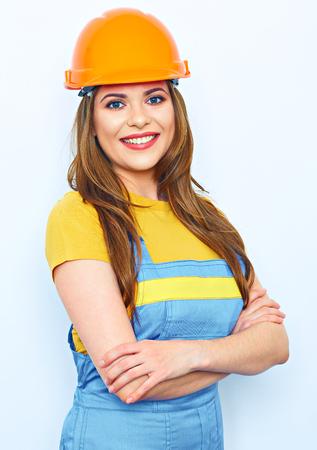 Glimlachende gekleed de bouwershelm van de vrouw. Vrouw in overall uniform.