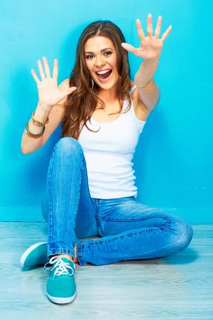 Positief emotioneel portret van jonge gelukkige vrouw op een vloer zitten