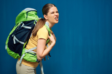 Tired girl with heavy backpack on blue background. Stock Photo