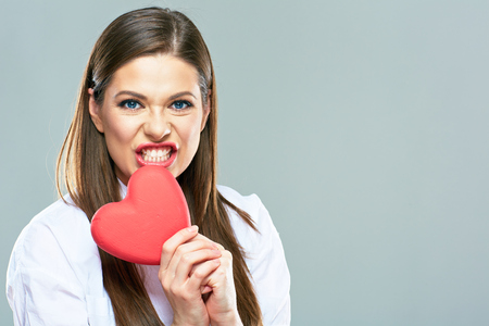 Heartbreakers woman portrait. Beautiful woman bite heart. Isolated portrait.