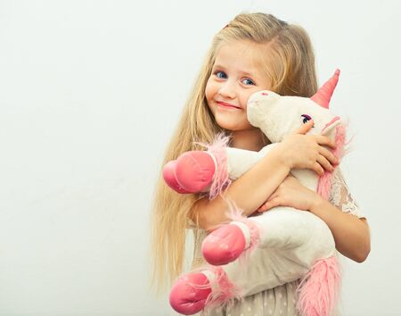 little smiling girl with white unicorn toy. isolated portrait of girl with long blond hair.