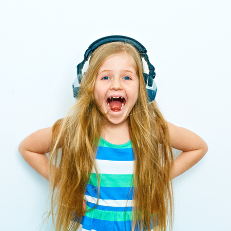 Screaming little girl with headphones funny portrait isolated on white background. Stock fotó