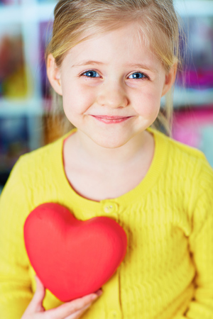 Little girl hold red heart. Home portrait. Stock Photo