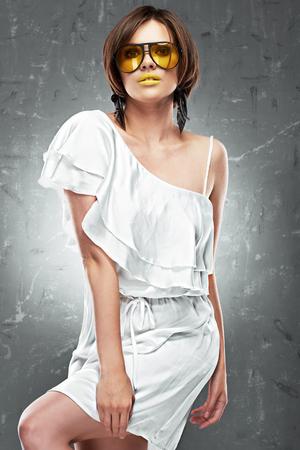 Fashion model. White dress. Yellow lips, sunglasses.