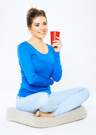 Young woman portrait with drink. Red coffee cup. Isolated white background.