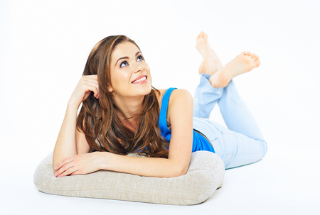 Smiling woman lying on a floor looking up. White background isolated.