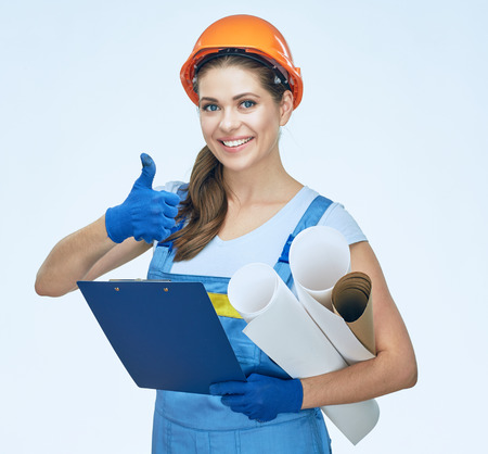 construction project: Woman builder holding blueprints, clipboard shows thumb up. Smiling architect girl. Isolated portrait. Stock Photo