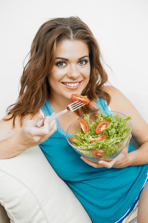 contemporary living room: Young woman with long hair sitting  on sofa at home and eating healthy food.
